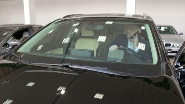 ein erfolgreicher Mann im Anzug telefoniert in seinem neuen Auto im Showroom