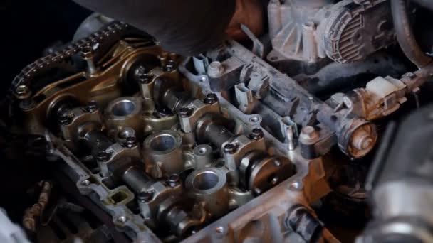 Uzavření mechaniky v rukavicích, opravuje motor v autě.