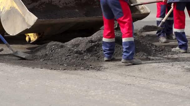 Dělníci odstraňují lopaty starý asfalt ze silnice pro pokládku nového asfaltu.