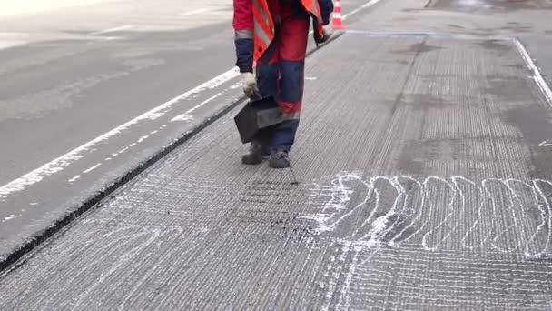 Opravy silnic. Pracovní údaje, dělníci nalít pryskyřice povrch vozovky na asfalt.
