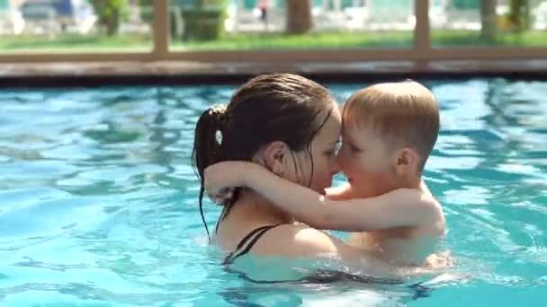 Šťastná máma se koupe v bazénu se svým malým synem, ona políbí dítě.
