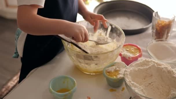 Malá holka v zástěře a čepici se učí vařit doma v kuchyni..