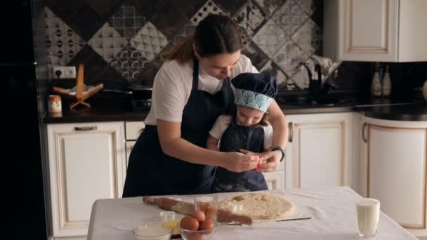 Matka a dcera vystřihly různé tvary sušenek z těsta v kuchyni.