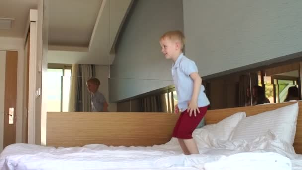 Close-up of a small happy boy 5 years old jumping on the bed in the bedroom.
