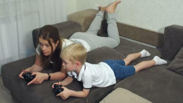 Emotionales Porträt von Mutter und Sohn zu Hause auf der Couch, sie spielen ein Videospiel.