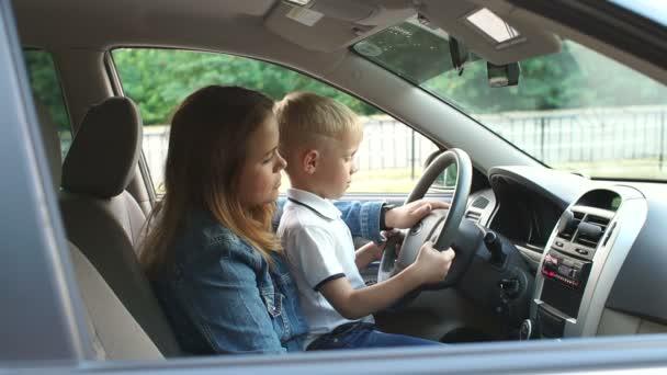 Malý chlapec sedící na matčině klíně za volantem a mačká roh.