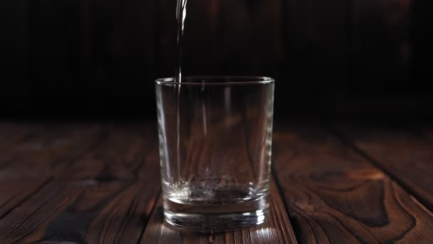 Close-up of whiskey poured into a glass on a wooden background, slow motion.