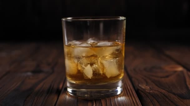 Egy maláta whisky jégkockákkal, fa háttéren. Közelkép. Lassú mozgás..