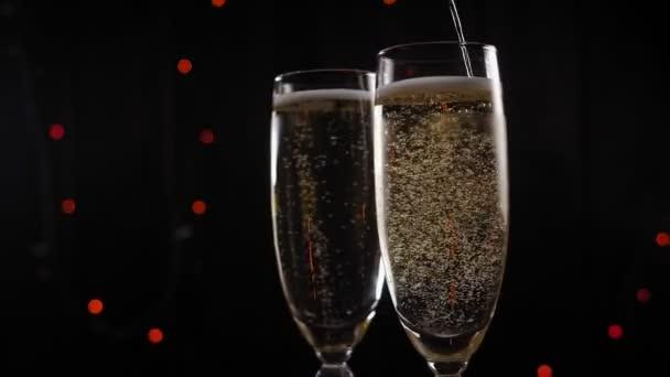 Detailní záběr dvou sklenic šampaňského pomalu rotující na černém pozadí.