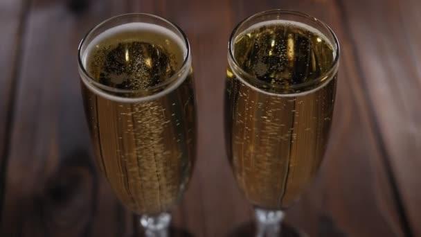 Detailní záběr dvou sklenic šampaňského s bublinkami na dřevěném pozadí.