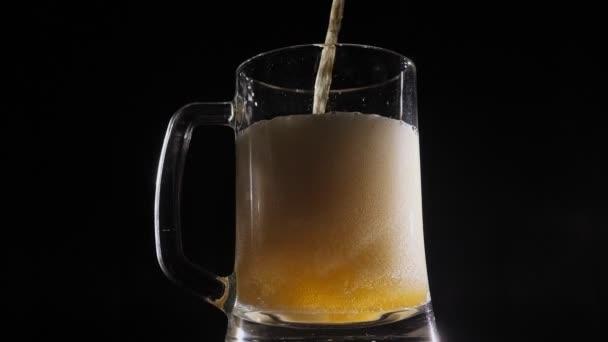 Detailní záběr piva nalil do pivního hrnku, který se pomalu otáčí na černém pozadí.