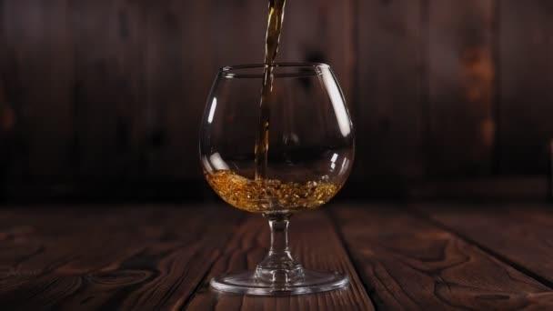 A konyakot üvegből üvegbe öntik, fa alapon. Lassú mozgás.