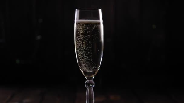 Nahaufnahme eines Champagnerglases, das sich langsam auf einem schwarzen Hintergrund mit Lichtern dreht