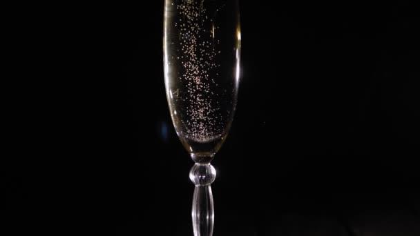 Großaufnahme eines Champagnerglases, das sich auf schwarzem Hintergrund um sich selbst dreht.