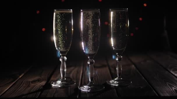 Három pezsgős szemüveg fekete háttérrel, sokszínű villogó fényekkel