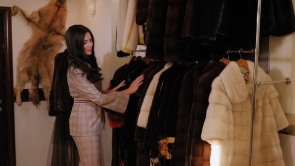 Luxusní elegantní žena si vybere nový kožich v dámském oblečení obchodě.
