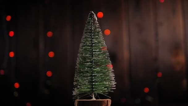 Vánoční strom pomalu točí kolem na dřevěném pozadí s blikajícími světly.
