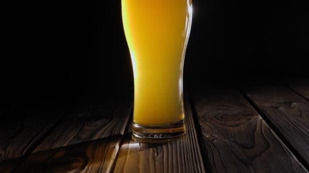 Detailní záběr čerstvého pěnového piva ve sklenici na černém pozadí. Zpomalený pohyb.