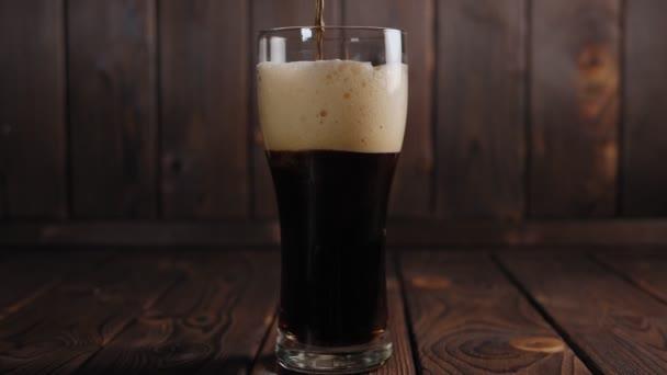 Detailní záběr, jak se tmavé pivo nalévá do sklenice na dřevěném pozadí, pomalu.