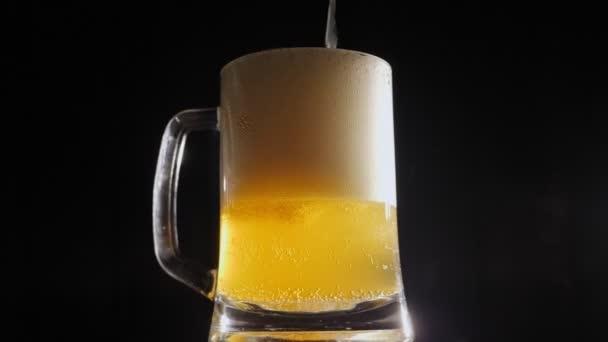 Egy sörkorsóba öntött sör közelről, ami lassan fekete hátteret ad..