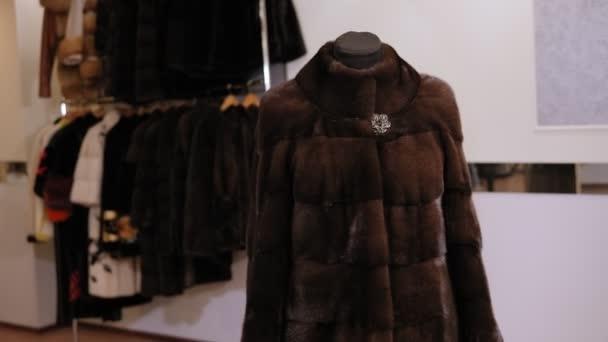 Krásný norkový kabát na figuríně v dámském obchodě s oblečením. Zpomalený pohyb.