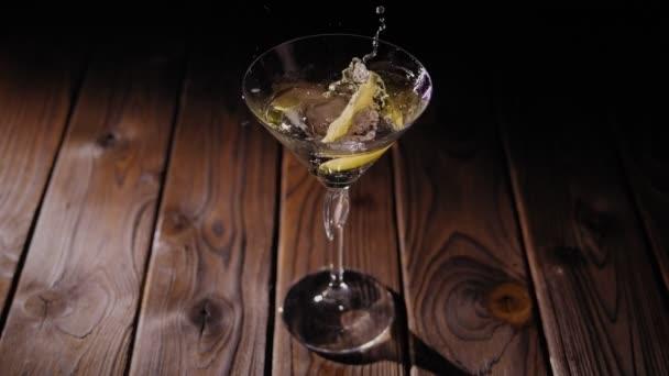 Nahaufnahme einer Zitrone oder Limette, die in ein Martini-Glas auf einem hölzernen Hintergrund fällt.