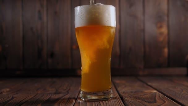 Detailní záběr piva nalitého do sklenice na dřevěném pozadí, hodně pěny.