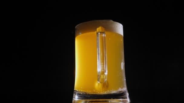 Světlé pivo v páře se pomalu otáčí na černém pozadí.