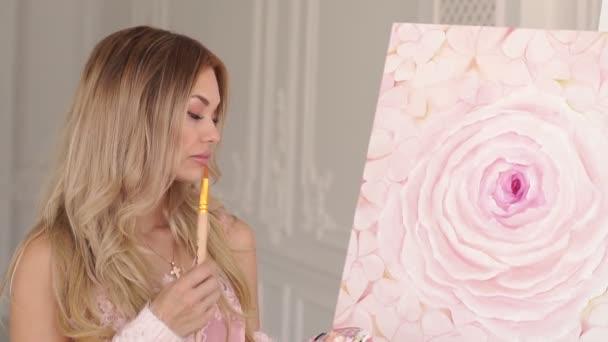 Egy lány művész pulóverben csodálja a festményét a rajzstúdióban..