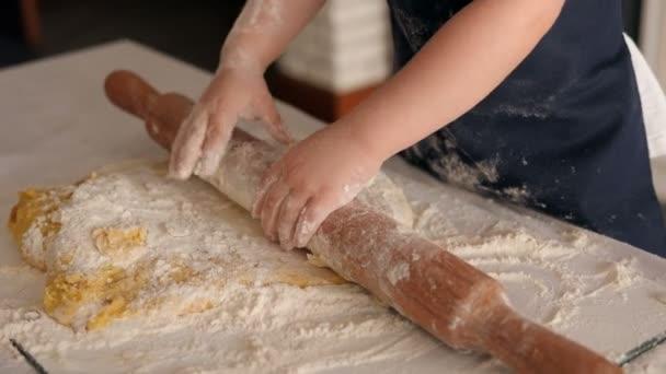 Közelkép a kislányról ügyetlenül gurítja a tésztát egy sodrófával a konyhán.