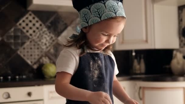 Close-up of a little charming girl smeared with flour claps her hands.