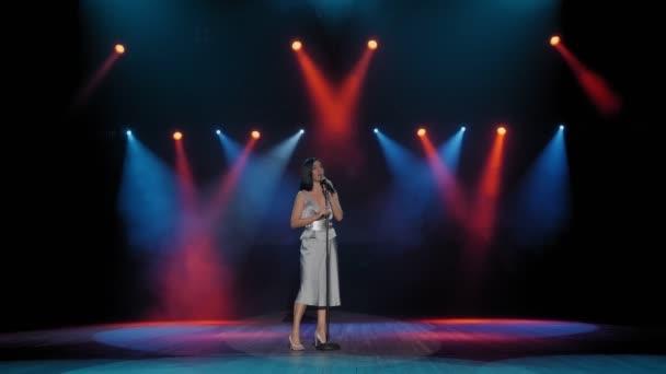 Egy énekesnő előad egy dalt a színpadon, színes keresőlámpákkal megvilágítva.