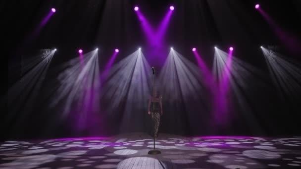 Egy nő hosszú ruhában felmegy a színpadra egy mikrofonhoz a sötétben..