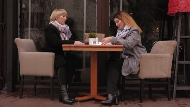 An elderly mother and an adult daughter sit at a table in street cafe with menu.