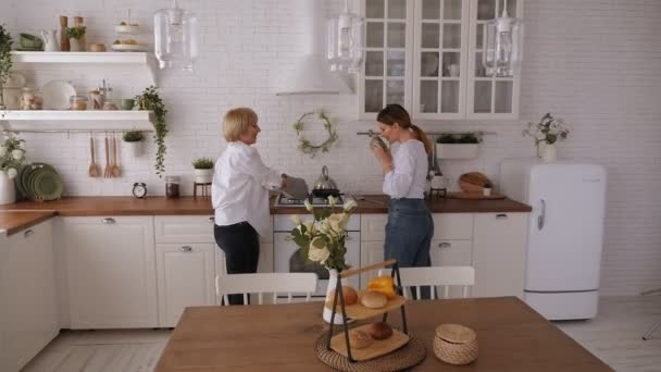 A happy old woman is preparing dinner with her adult daughter in the kitchen.