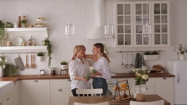 Mladá žena pije čaj se starší matkou doma v moderní kuchyni.