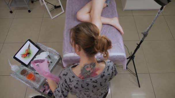 Cool lány tetoválás mester tetoválás gép csinál egy tetoválás egy lány.