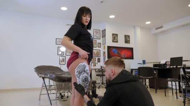 Tetováló művész tesz egy képet a lábát egy lány, folyamat létrehozása egy tetoválás.