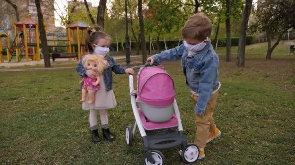 Kleine Kinder in medizinischen Masken spielen im Park mit einem Kinderwagen. Coronavirus.