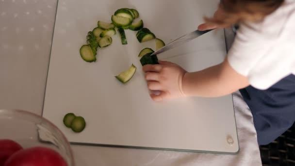 Közelkép a kislányról, aki friss uborkát vág, segít az anyjának vacsorát főzni.