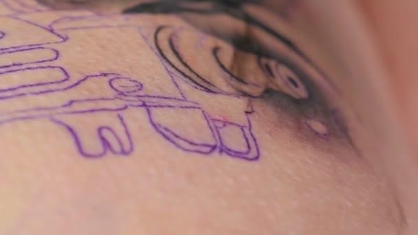 A tetoválógépek fekete tintát fecskendeznek a nő bőrébe. Tetoválást csinál.