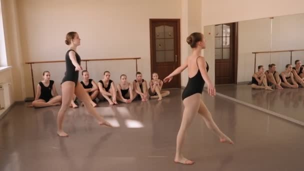 Dvě ohebné mladé baletky skákají do štěpů v baletní třídě.Balet