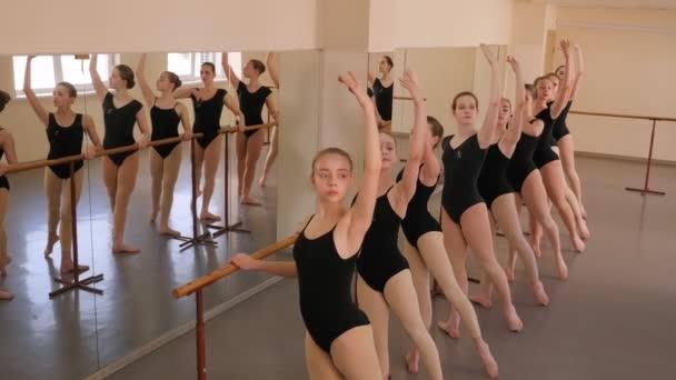 Ballerinas simultaneously show a choreographic exercise in a ballet class.