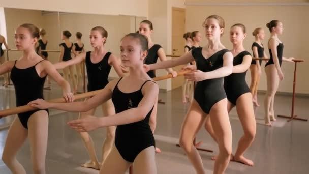 Young ballerinas rehearse a choreographic exercise at a ballet school.