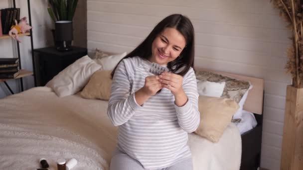 Těhotná žena sedí na posteli v ložnici a drží hodně prášků.