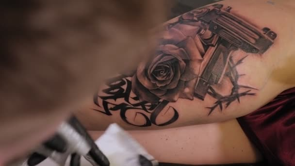 Jehlové tetovací stroje vstříknou černý inkoust do kůže ženy. Udělá tetování.