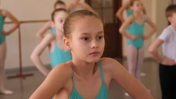 Little girls and one boy warming up before a ballet lesson at a ballet school.