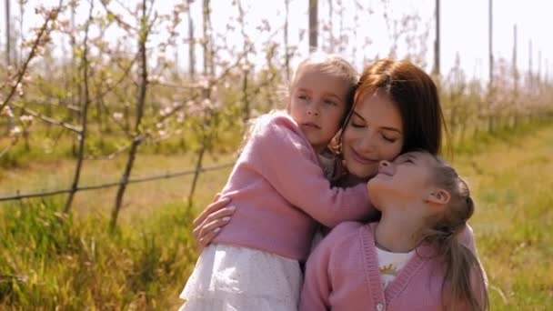Portrait of a young mother with twin daughters in a spring Apple orchard.