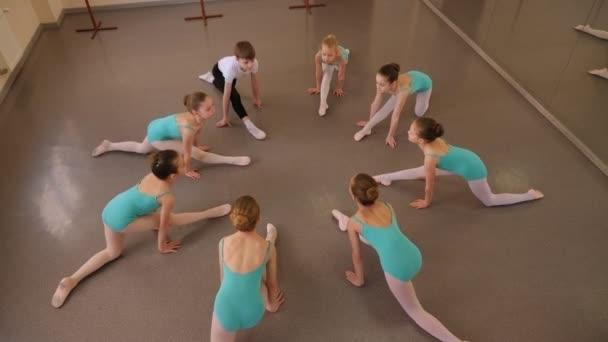 Rugalmas gyerekek ülnek hasadékokban egy körben a padlón egy táncstúdióban..
