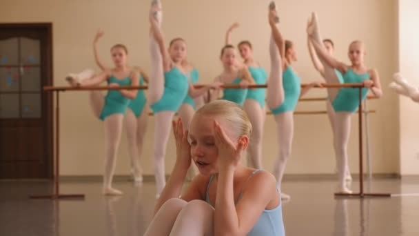Young ballerina is crying. Tears of a little ballerina in a ballet school.